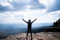 A person hands up standing on rocky mountain looking out at scenic natural. View and beautiful blue sky royalty free stock photography