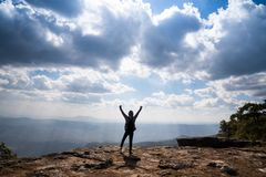 A person hands up standing on rocky mountain looking out at scenic natural. View and beautiful blue sky stock photos