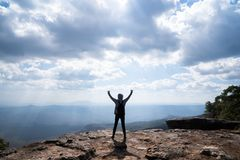 A person hands up standing on rocky mountain looking out at scenic natural view. And beautiful blue sky royalty free stock photos