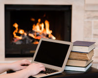 Person hands using laptop  on the background of the fireplace Stock Photos