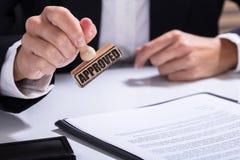 Person Hands Using Stamper On dokument med den godkända texten arkivbild