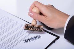 Person Hands Using Stamper On dokument med den godkända texten arkivfoto