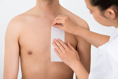 Person Hands Waxing Man's Chest. Close-up Of Person Hands Waxing Man's Chest With Wax Strip Stock Photo
