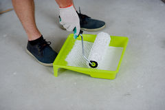 The person has dipped the roller in a tray with paint. On a gray concrete floor there is a yellow tray. In him white paint. The hand in a working glove dips the Stock Image