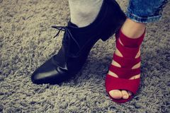 Person has a lady`s boot on one leg, and on the other a male boot. Man or woman? Person has woman´s red sandal and men´s black formal shoe.Gender conflict stock photo