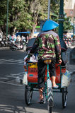 Person with hat riding Tricycle on asian street Stock Photos