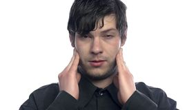 Person having headache on white background. Portrait of attractive male with headache trying to mitigate with hands stock video footage