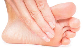 Person having pedicure, pulling hand under foot towards white ba Stock Photos