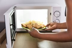 Person Heating Fried Food In Microwave Oven. Close-up Of A Person`s Hand Heating Fried Food In Microwave Oven royalty free stock photo