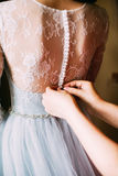 Person help to a bride to clasp buttons of the dress Stock Photos