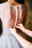 Person help to a bride to clasp buttons of the dress Royalty Free Stock Photo