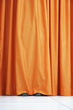Person Hiding Behind Orange Curtain Stock Image