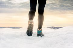 Person hiking on the mountaintop covered with snow. Low angle view Royalty Free Stock Photos
