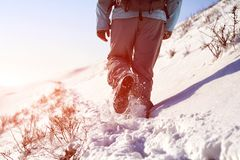 Person hiking on the mountaintop covered with snow low angle view. Man is doing outdoor activities. Supporting healthy lifestyle. Footprints on the snow Royalty Free Stock Image