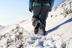 Person hiking on the mountaintop covered with snow low angle view. Man is doing outdoor activities. Supporting healthy lifestyle. Footprints on the snow Royalty Free Stock Photo
