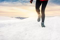Person hiking on the mountaintop covered with snow. Low angle view Royalty Free Stock Photo