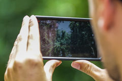 Person with his mobile device is trying to capture a memorable moments in a wild nature while swiming in the river. Hands of a man holding a black android Stock Photos