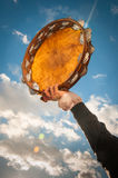 Person holding aloft a tambourine against blue sky. Arm of a person holding aloft a tambourine shaking it to prduce jingling music during a fiesta or carnival in Stock Photography