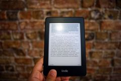 Person Holding Amazon Kindle Ebook Royalty Free Stock Photos