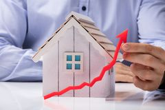 Free Person Holding Arrow In Front Of House Model Stock Image - 126304131
