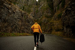 Person Holding Back Pack Walking Black Asphalt Road Stock Images