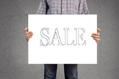 Person holding banner with SALE message. Royalty Free Stock Images