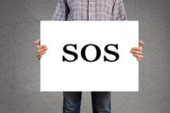 Person holding banner with SOS message. Person holding white banner with SOS message royalty free stock images