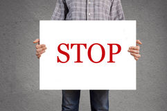 Person holding banner with STOP message Royalty Free Stock Photo