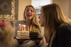 Young woman holding birthday cake with glowng candles. Person holding birthday cake while another person is blowing out the candles at family party Stock Photos
