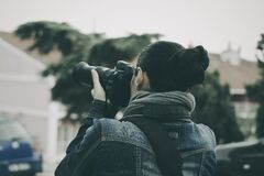 Person Holding Black Dslr Camera Wearing Blue Denim Jacket Stock Photo