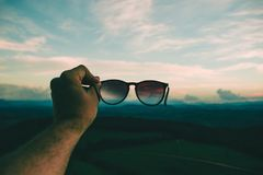 Person Holding Black Framed Sunglasses Under Blue Sky and White Clouds royalty free stock photo