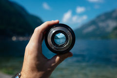 Person Holding Black and Gray Round Scope Viewing Mountain Cliff Near Body of Water during Daytime Stock Photo