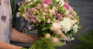 Person holding bouquet. Close-up shot of anonymous crop person holding big arranged bouquet in hands composed of different flowers stock footage