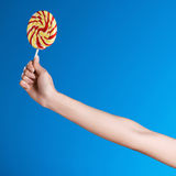Person holding bright lollipop isolated on blue. Cropped shot of person holding bright lollipop isolated on blue Stock Image