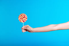 Person holding bright lollipop isolated on blue Royalty Free Stock Photos