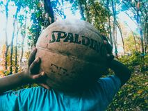 Person Holding Brown Spalding Basketball Stock Image