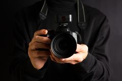 Person holding a camera close up. Person holding a DSLR camera close up stock photo