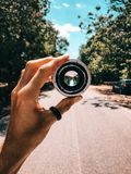 Person Holding Camera Lens in the Middle of Street Under Blue Sky Stock Image