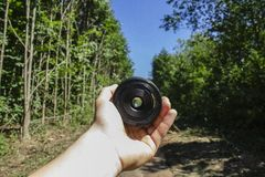 Person Holding Camera Lens in Woods stock images