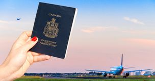 Person holding a Canadian passport with one airplane taxiing and another taking off stock photography