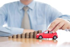 Person Holding Car Over Rising Coins. Person Holding Car Over Rising Stacked Coins royalty free stock image