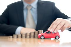 Person Holding Car Over Rising Coins. Person Holding Car Over Rising Stacked Coins stock image