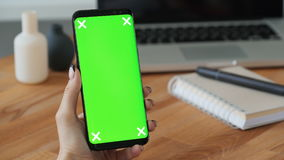 Person holding cellphone with greenscreen display in hand stock footage