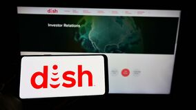 Person holding cellphone with logo of television company DISH Network Corporation on screen in front of business webpage.