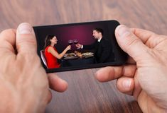 Person holding cellphone watching video stock photo