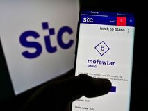 Person holding cellphone with webpage of Arabian carrier Saudi Telecom Company (STC) on screen in front of logo.