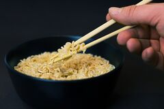 Person Holding a Chopsticks and Picking a Noodles in Black Bowl Stock Images
