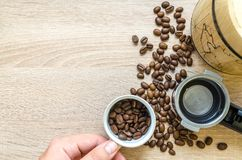 Person Holding Coffee Cup With Coffee Beans Near Coffee Press Stock Photos