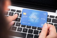 Person holding credit card using laptop Stock Image