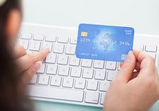 Person holding credit card using laptop. Close-up Of A Person Holding Credit Card Using Laptop Stock Images